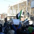 على نهج الأسد ... تحرير الشام تداهم بنش وتحرق علم الثورة